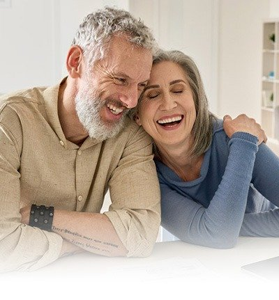 middle age couple laughing at the kitchen counter