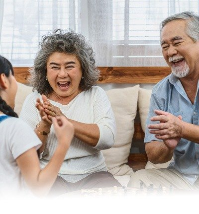 older asian couple laughing with their granddaughter